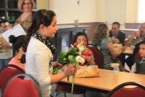 Een aanwezige kind deelt bloemen uit